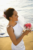 Bride+holding+bouquet+on+beach.