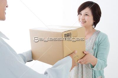 荷物を受け取るミドル女性の写真...