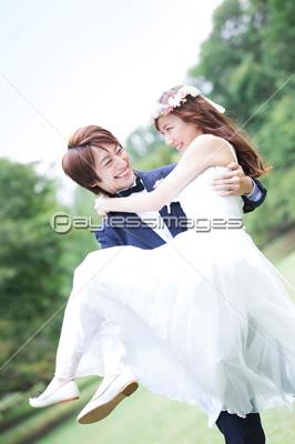お姫様抱っこする新郎新婦の写真・イラスト素材 (af9920079173