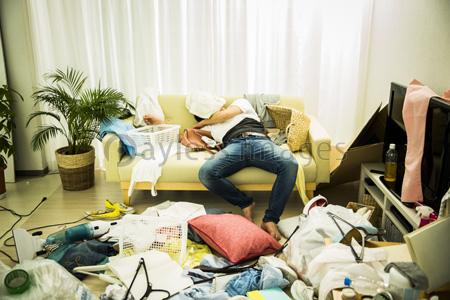 散らかった部屋で項垂れる男性の写真イラスト素材 Af9940108876
