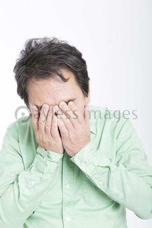 顔を手で覆う男性の写真・イラス...