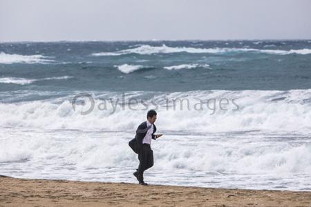波打ち際を歩くビジネスマンの写真イラスト素材 Gf1420773091