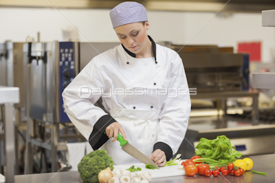 Serious chef using digital tablet beside the vegetables