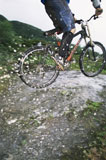 Man+outdoors+on+trails+jumping+bicycle+over+puddles+%28selective+focus%29