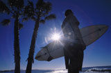 Silhouette+of+a+man+holding+a+surfboard+standing+on+a+beach