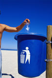 Mid+section+view+of+a+young+man+throwing+a+bottle+into+a+garbage+can+on+the+beach